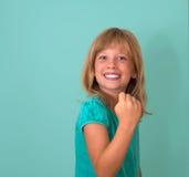 成功 赢取成功小女孩愉快欲死欲仙庆祝的画象是优胜者隔绝了绿松石背景 正 免版税库存图片