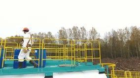 成套装备的雇员爬上梯子对与化学制品的坦克由桦树 股票视频