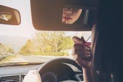 组成她的面孔的妇女使用唇膏,当驾驶汽车时 图库摄影