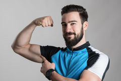 成就概念 显示二头肌力量的年轻骑自行车者画象微笑对照相机 免版税图库摄影