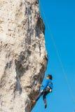成年男性在垂直的平的墙壁上的攀岩运动员侧视图有恶劣的安心的 库存照片