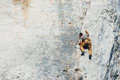 成年男性在垂直的平的墙壁上的攀岩运动员侧视图有恶劣的安心的 免版税库存图片