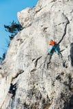 成年男性在垂直的平的墙壁上的攀岩运动员侧视图有恶劣的安心的 Gora Zborow是a 库存照片