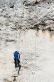 成年男性在垂直的平的墙壁上的攀岩运动员侧视图有恶劣的安心的 Gora Zborow是a 库存图片