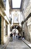 成拱形与在城市的中心连接鹅卵石一个狭窄的胡同的两个房子和与人的窗口和阳台 免版税库存图片