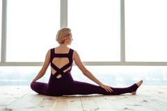 成拱形她的腰部的勤勉年轻体操运动员,当倾斜时 免版税库存图片