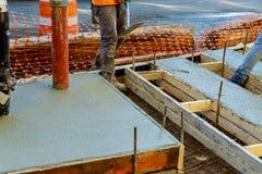 成水平混凝土路面的建筑工人 倾吐的混凝土路面 图库摄影