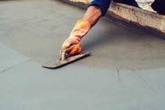 成水平混合水泥的工作者混凝土路面在建筑 免版税库存图片