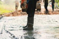 成水平混合水泥的工作者混凝土路面在建筑 免版税图库摄影