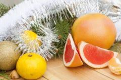 成熟与新年的和圣诞节装饰中间的裁减红色葡萄柚结果实和闪亮金属片 免版税库存照片