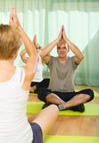 成熟与辅导员的夫妇实践的瑜伽 免版税图库摄影
