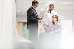 成熟专家谈话与轮椅的患者在医院 免版税库存照片