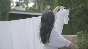 成熟主妇妇女在一好日子垂悬在晒衣绳的被洗涤的干净的洗衣店她的房子外 ??  影视素材