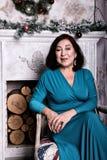 成熟亚裔妇女坐在豪华礼服的椅子 库存图片