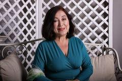 成熟亚裔妇女坐在豪华礼服的长沙发 库存图片