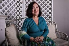 成熟亚裔妇女坐在豪华礼服的长沙发 库存照片