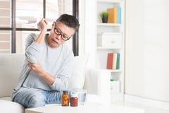 成熟亚洲人手肘痛苦 免版税库存图片