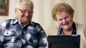 成熟享受现代技术的资深夫妇使用片剂个人计算机 在家沟通与互联网的老年人 股票录像