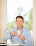 成熟享用咖啡的人,当在工作时 库存图片