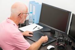 成熟人与图形输入板一起使用在他的办公室 免版税库存照片