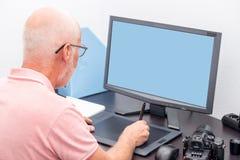 成熟人与图形输入板一起使用在他的办公室 免版税图库摄影