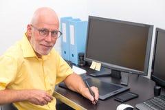 成熟人与图形输入板一起使用在他的办公室 库存照片
