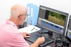 成熟人与图形输入板一起使用在他的办公室 库存图片