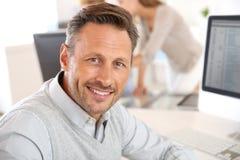 成熟人与计算机一起使用在办公室 免版税图库摄影