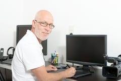 成熟人与他的计算机一起使用 免版税库存照片