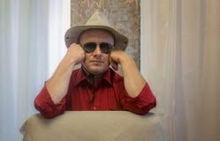 成熟人佩带的帽子和黑太阳镜画象  免版税库存图片