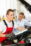 成熟人和女性汽车修理师在讨论会 库存照片