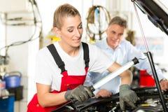 成熟人和女性汽车修理师在讨论会 库存图片
