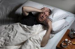 成熟人在物理痛苦中,当设法睡着时 免版税库存照片