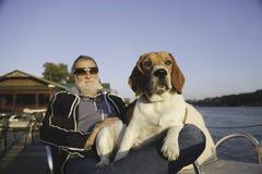 成熟人坐一件清楚的晴天藏品的一个河岸 免版税库存图片