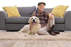 成熟人坐与他的狗的地板 库存照片