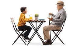 成熟人坐在咖啡桌上和谈话与他的孙子 免版税库存照片