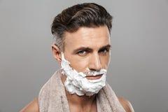 成熟人身分隔绝与在面孔的剃须膏 库存图片