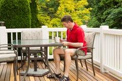 成熟人读书外面在露台 免版税库存图片