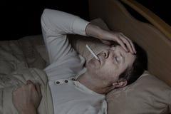 成熟人以高烧在床上 免版税图库摄影