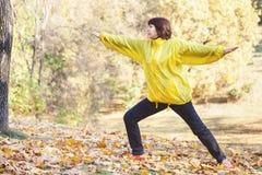 成熟俏丽的妇女参与体操在秋天森林里 免版税库存照片