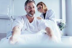 成熟做核对的人坐在医院病床上的和医师 库存图片