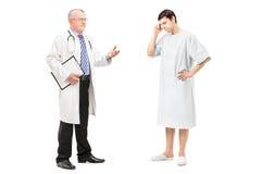成熟健康专家谈话与一名担心的患者 免版税库存图片