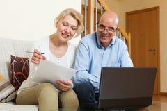 成熟加上膝上型计算机在家 免版税库存图片
