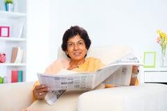成熟印第安妇女读取新闻纸张 免版税库存照片