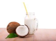 成熟和开胃椰子和新鲜的牛奶在一个金属螺盖玻璃瓶在一张木桌上,在白色背景 异乎寻常的椰子 库存图片