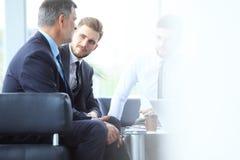 成熟商人使用数字式片剂与一个更加年轻的同事谈论信息在一个现代企业休息室 库存图片