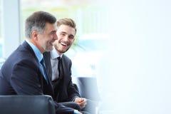 成熟商人使用数字式片剂与一个更加年轻的同事谈论信息在一个现代企业休息室 免版税库存图片