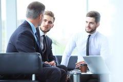成熟商人使用数字式片剂与一个更加年轻的同事谈论信息在一个现代企业休息室 库存照片