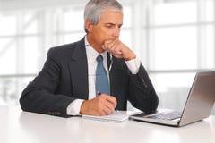 成熟商人安装与膝上型计算机 免版税库存照片