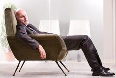 成熟商人睡着在扶手椅子 库存图片